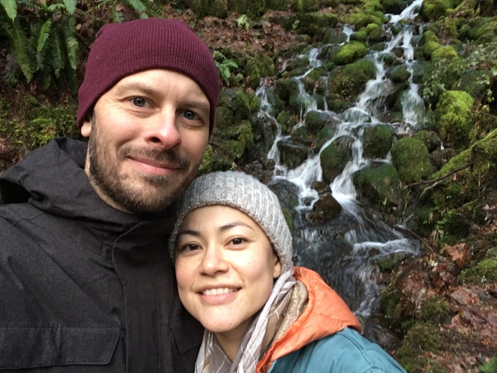 My partner and I, wearing beanies and raincoats, smiling in front of a waterfall. The rocks are covered with soft green moss.